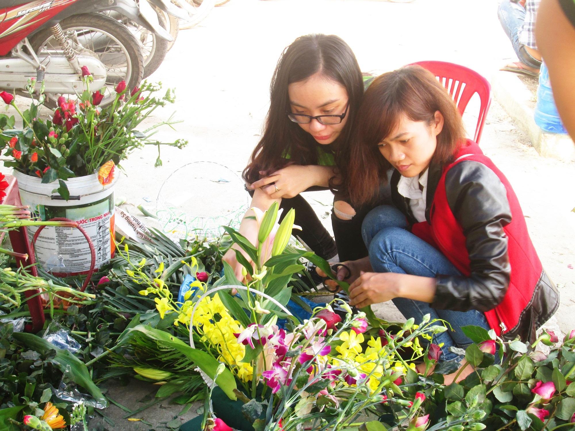"""2 """"thợ cắm hoa nghiệp dư"""" của nhóm đang thảo luận cách cắm hoa sao cho đẹp"""