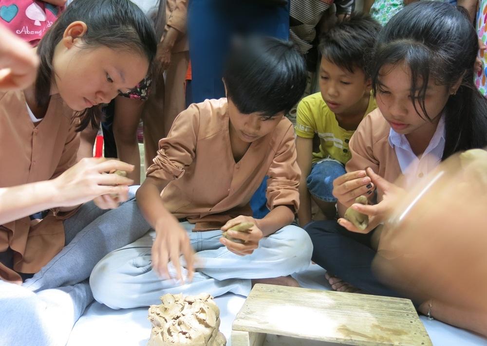 Các em nhỏ học nặn tượng gốm