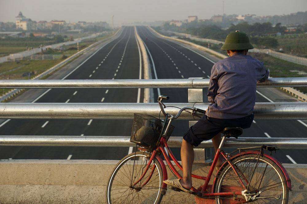 Một người dân đang nhìn ngắm đoạn đường chạy qua địa phận huyện Văn Giang, tỉnh Hưng Yên đã hoàn thành nhưng chưa đưa vào khai thác. 6 làn đường chính chỉ dành cho xe ô tô, các loại phương tiện khác sẽ đi theo 2 đường gom 2 bên kết nối các đường dân sinh, tổng chiều dài đường gom là 164,8km.