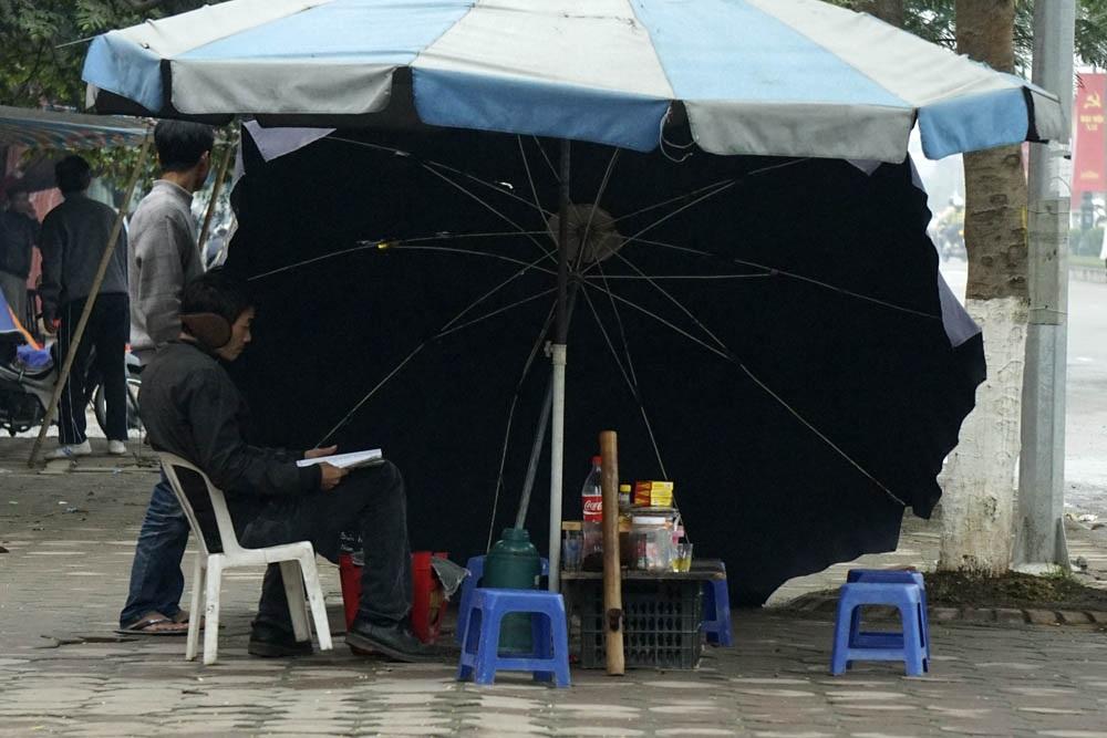Một quán cóc ven đường nghiêng ô không để che nắng mà để chắn đợt gió mùa ào ạt thổi.