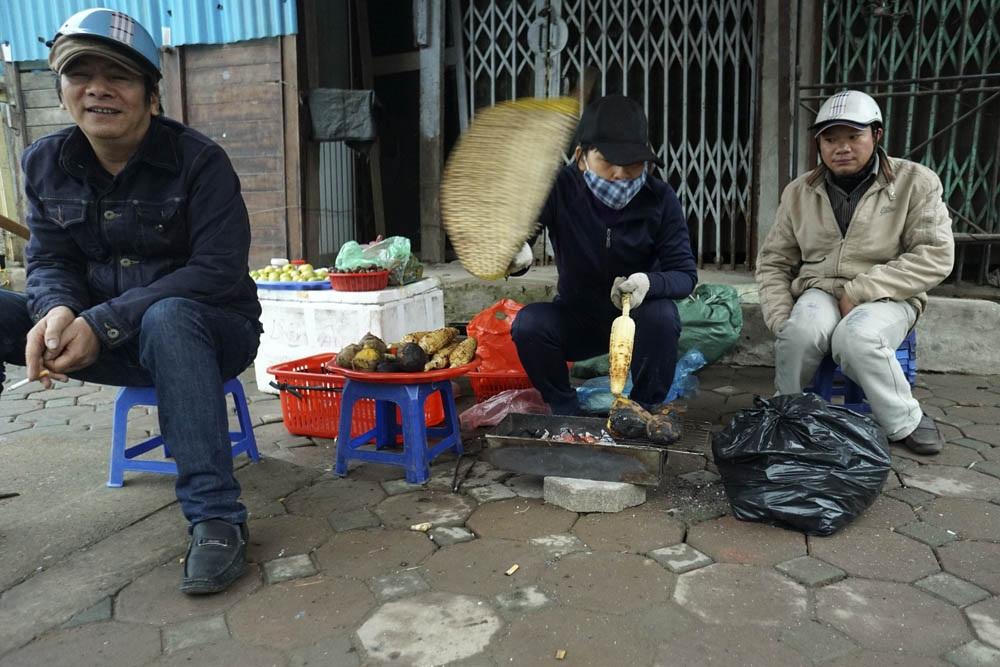 Nhiều người ở ngoài đường co ro bên bếp than nướng ngô.