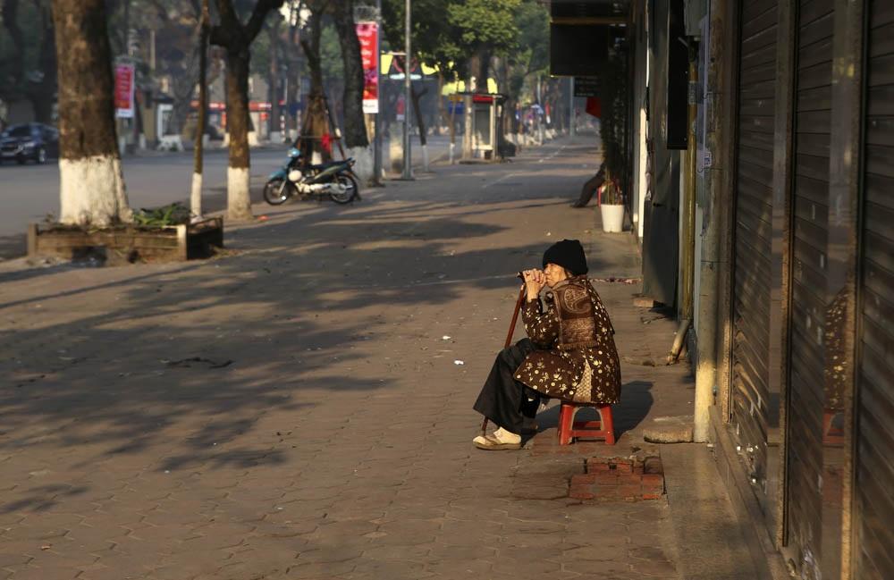 Một bà cụ ngồi phơi nắng trong buổi sáng ngày đầu năm.