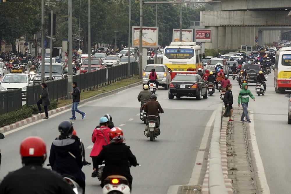 Ở vị trí đường dẫn lên cầu vượt Ngã Tư Sở có mật độ dân cư đông đúc, người dân xé rào để sang đường.