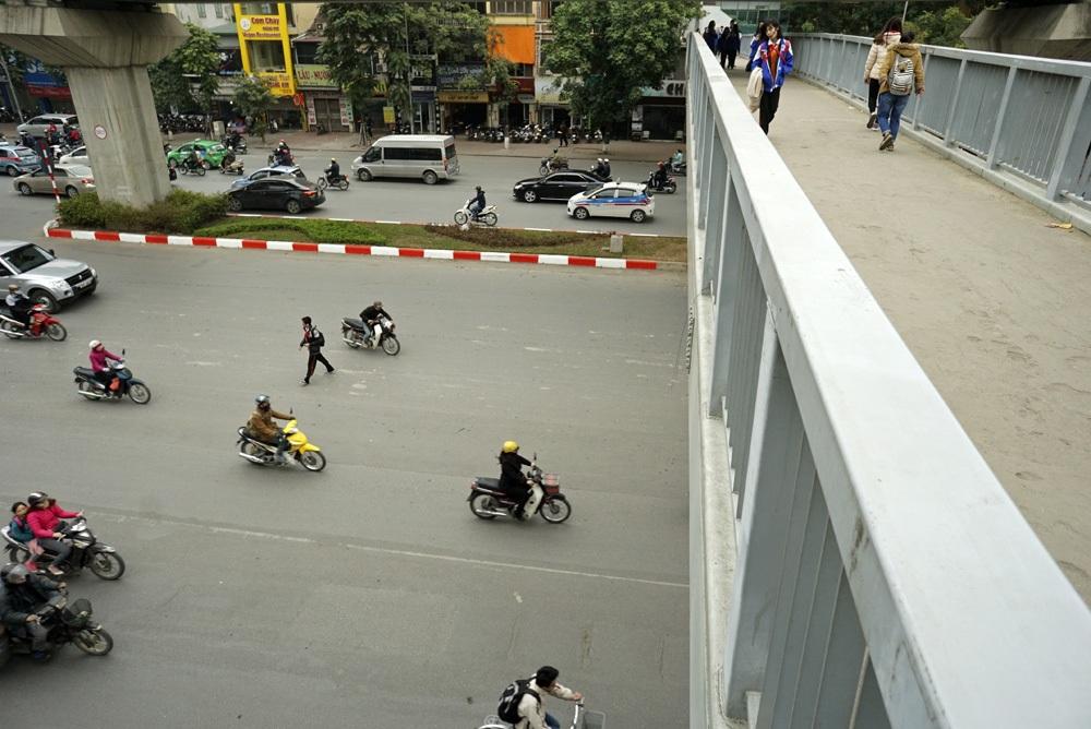 Ngay tại chân một cầu vượt đi bộ trên phố Nguyễn Trãi (quận Thanh Xuân), một số người vẫn đi bộ qua mặt đường theo thói quen.