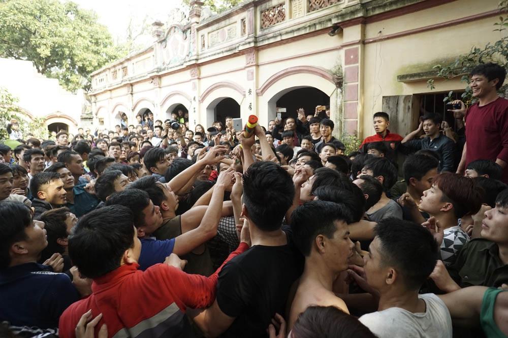 Sau đó cây bông được tung ra, hàng trăm thanh niên lập tức ào vào giành giật.