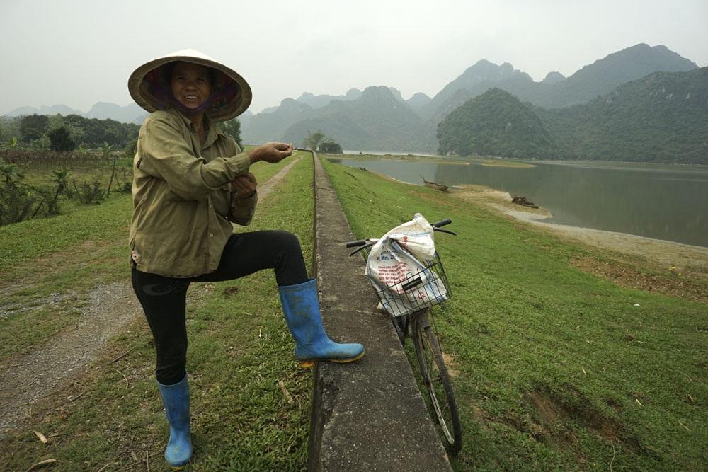 Còn đây là chị Phùng Thị Chuyển ở thôn Quýt 2, chị vừa lội qua hồ để vào núi thăm đàn dê đang chăn thả. Nhà chị đấu thầu 15 ha đất rừng trong dãy núi ở vùng hồ Tuy Lai để nuôi bò và dê với giá 2 triệu đồng/năm.