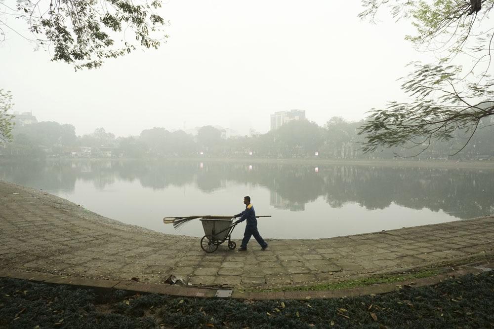 Một người công nhân môi trường đang thu gom rác trên mặt hồ Thiền Quang phủ đầy sương trắng.