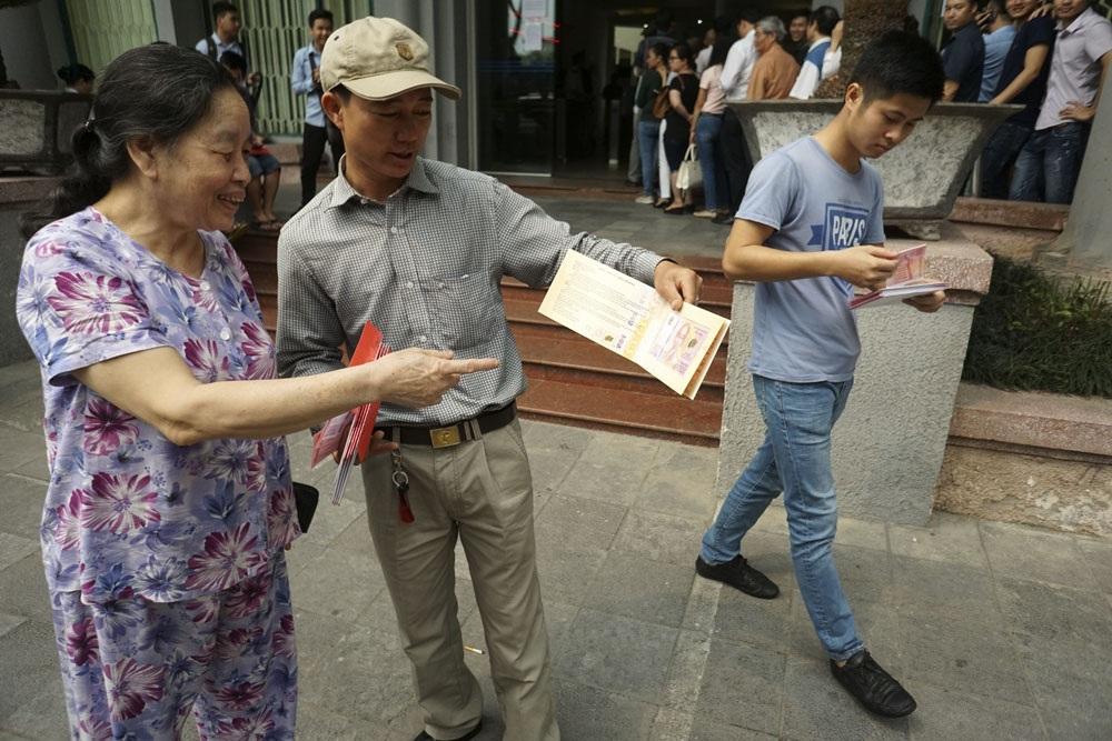 Anh Nguyễn Văn Thuận hành nghề xe ôm đang hào hứng trưng ra loại tờ tiền dạng foder có giá bán 25 nghìn đồng/tờ. Anh cho biết đã xếp hàng từ 7 giờ đến 10 giờ mới mua được 25 tờ, và khi có người hỏi mua lại anh nói bán với giá 50 nghìn/tờ.
