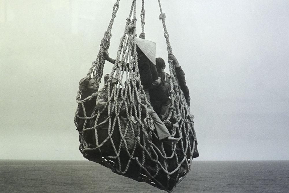 Lưới hàng cẩu người tỵ nạn từ một xà lan lên tàu SS Pioneer Contender để sơ tán khỏi Đà Nẵng. Phải mất 8 tiếng tàu này mới đưa được khoảng 6000 người lên tàu, 30/3/1975. Ảnh chụp của Peter OLoughlin.