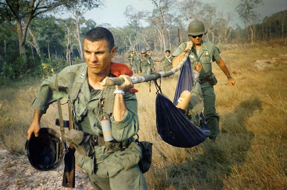 Trong phần 1 Cuộc chiến ác liệt là nhiều hình ảnh của các phóng viên Hãng AP cho thấy sự khốc liệt của cuộc chiến. Trong ảnh, một cố vấn Mỹ dùng bạt làm võng để đưa một người lính bị thương tới một máy bay trực thăng Mỹ để về Sài Gòn 9/1965. Ảnh tư liệu của AP.