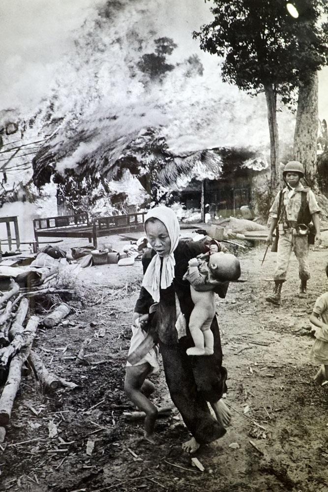 Một phụ nữ Việt Nam bế một em bé trên tay và kéo theo con gái chạy tới nơi trú ẩn sau khi ngôi nhà của họ bị Quân đội Việt Nam Cộng hòa đốt cháy ở gần Tây Ninh, cách Sài Gòn 96km về phía Tây Bắc 7/1963. Ảnh chụp của Horst Faas.