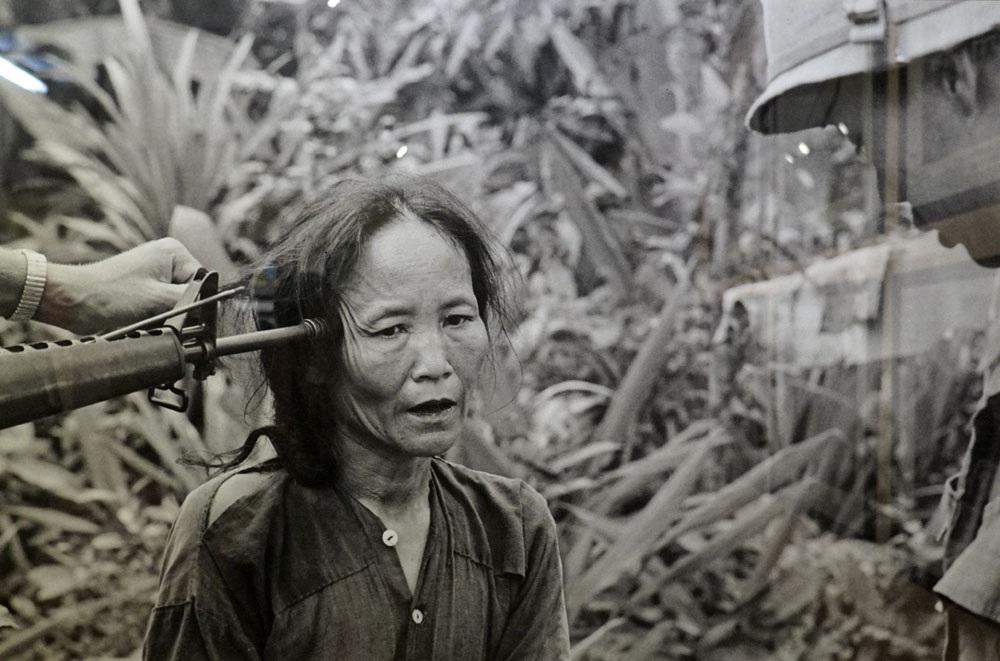 Một người phụ nữ Việt Nam bị tình nghi là Quân giải phóng đang bị tra khảo dưới họng súng của một sỹ quan cảnh sát Nam Việt Nam tại Tam Kỳ 11/1967. Ảnh tư liệu của AP.