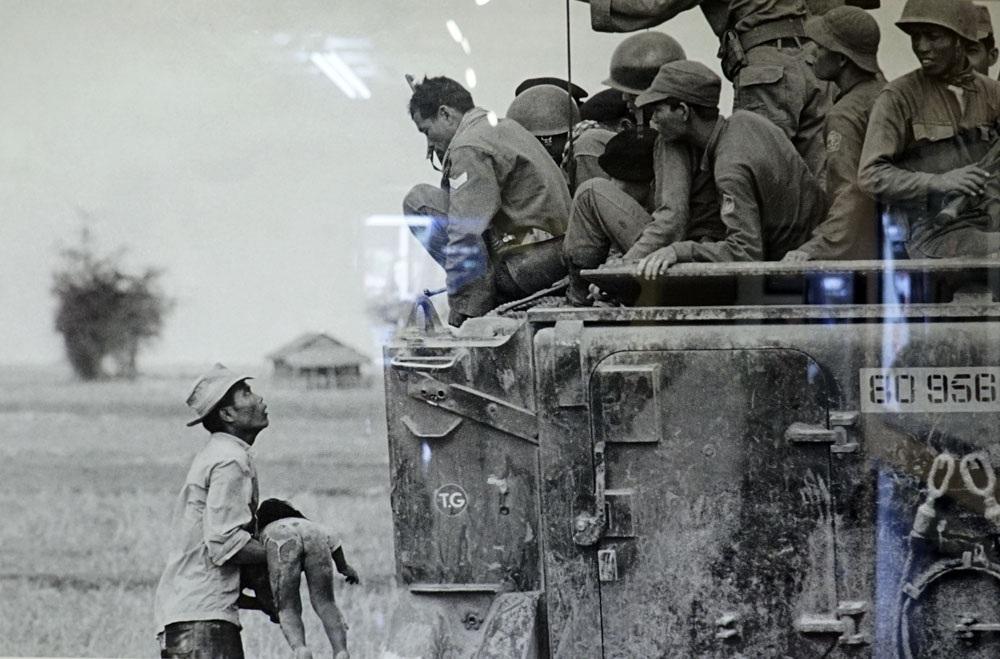 Một người cha người Việt Nam đau đớn ôm thi thể của con mình trong khi lính biệt kích Việt Nam Cộng hòa nhìn xuống từ xe bọc thép ngày 19/3/1964. Ảnh chụp của Horst Faas.