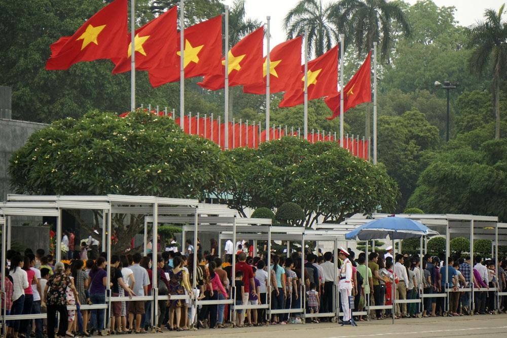 Dòng người chờ vao viếng Bác dưới hàng cờ đỏ sao vàng tung bay trên khán đài.