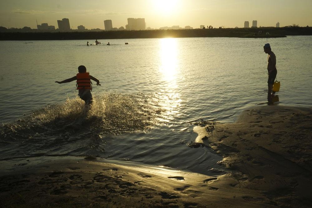 Người lớn cho trẻ nhỏ mặc áo phao và giám sát chặt chẽ trong lúc chơi đùa dưới làn nước sông Hồng mát mẻ.