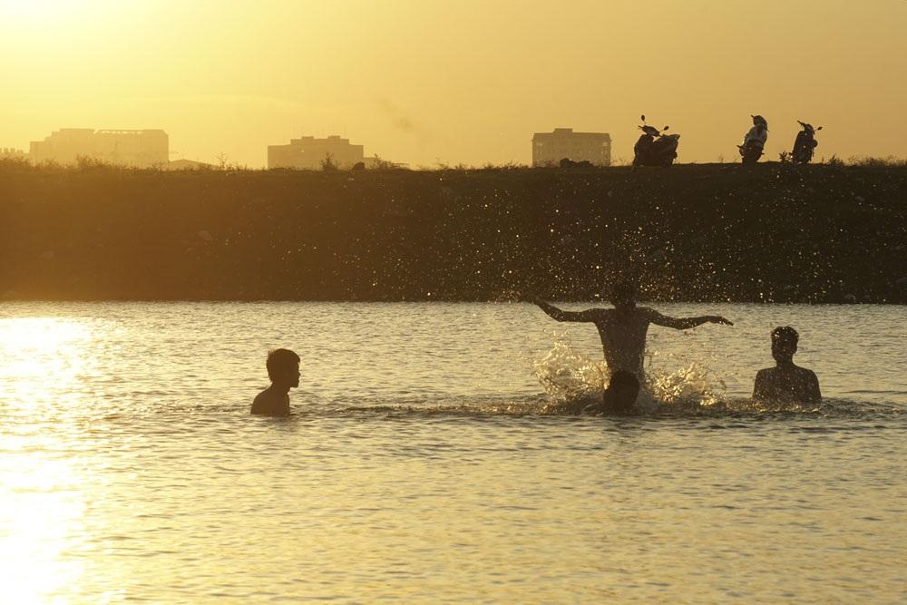 Những thanh niên đang vùng vẫy dưới làn nước mát trong buổi chiều nóng nực.