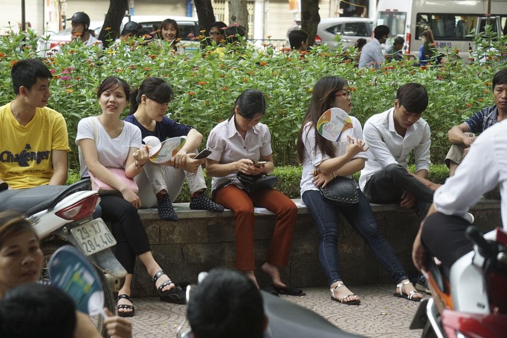 Các phụ huynh quyết tâm chờ đợi con ngoài cổng trường trong thời gian thi.