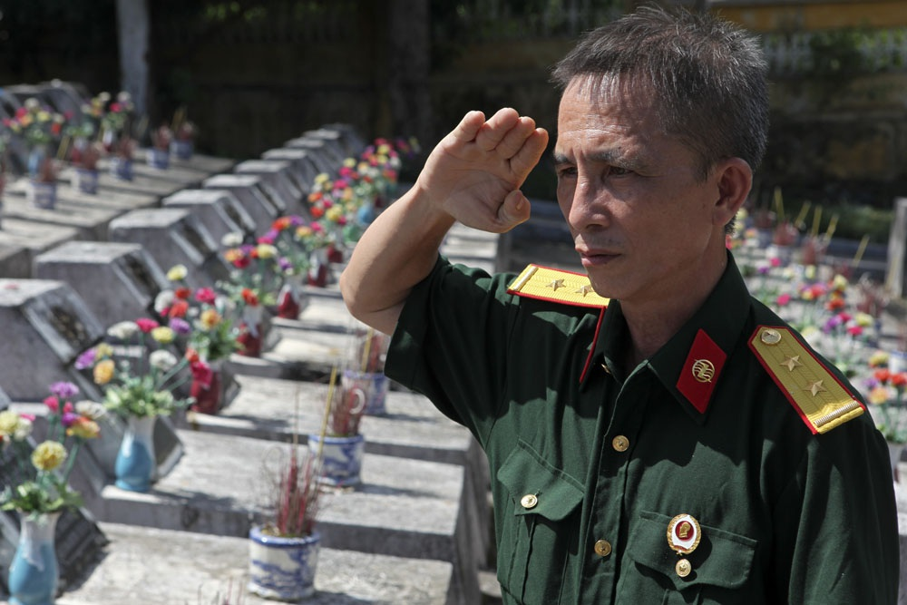 Cựu binh của sư đoàn 356 Phạm Quang Hòa chào đồng đội sau khi thắp hương lên mộ liệt sỹ ở nghĩa trang Vị Xuyên.