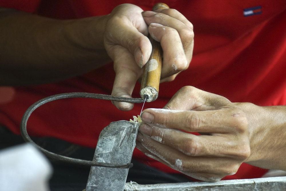 Một thợ thủ công đang gia công các chi tiết cho bộ đồ gỗ chạm ốc cầu kỳ với nhiều chi tiết cực nhỏ. Đây là buổi trình diễn của nhóm thợ thủ công làng nghề sản xuất đồ gỗ mỹ nghệ xã Chuyên Mỹ (Phú Xuyên, Hà Nội).