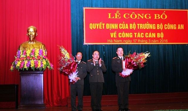 Thượng tướng Bùi Quang Bền trao quyết định, tặng hoa chúc mừng Đại tá Nguyễn Văn Trung và Đại tá Phạm Hồng Tuyến (Ảnh: Công an Hà Nam)