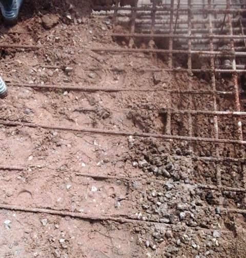 Phần móng đổ bê tông chỉ bỏ một phần xi măng vào trộn cùng đá sỏi, phần còn lại là đất cho xuống phần đế móng (ảnh cắt từ clip)