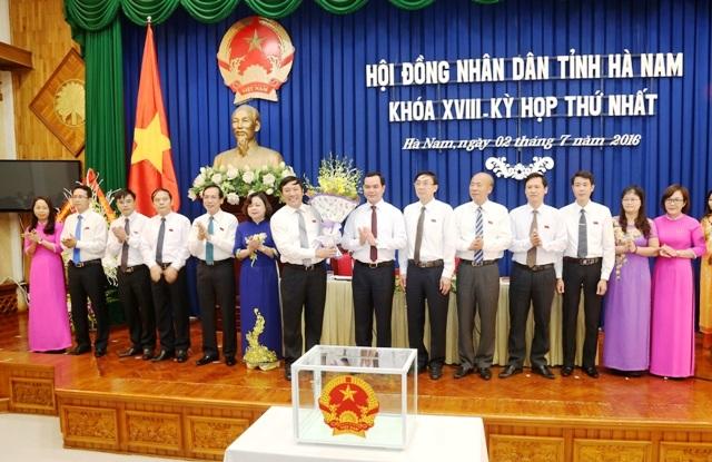 Ông Nguyễn Đình Khang, Bí thư Tỉnh ủy Hà Nam tặng hoa chúc mừng ông , ông Phạm Sỹ Lợi