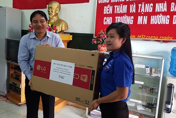 Anh Nguyễn Đắc Vinh (trái) tặng quà cho trường mầm non Hướng Dương