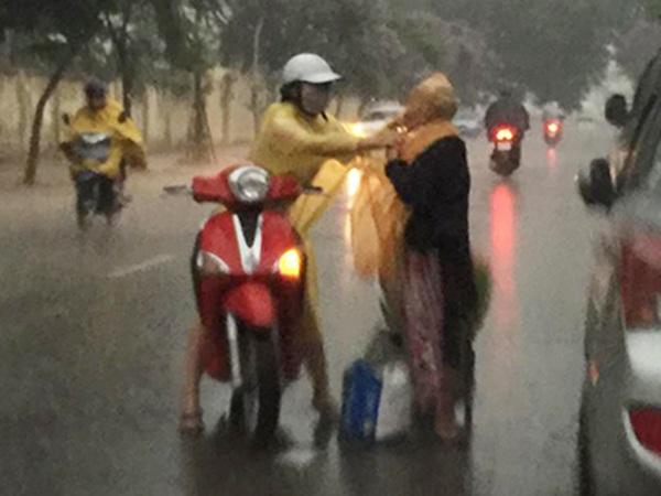 Cô gái tự tay mặc áo mưa cho bà cụ đi đường