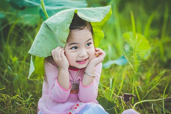 Những bức ảnh bé Vũ Bảo Ngọc (4 tuổi) hé nụ cười dưới tán lá sen khiến người xem yêu thích.