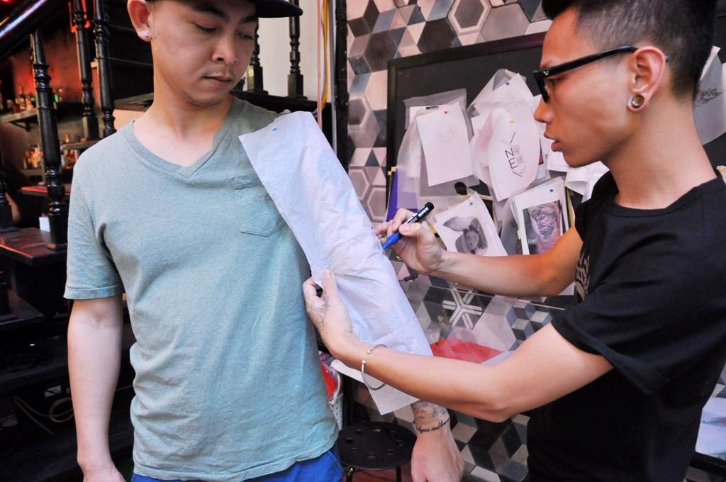 Anh Đạt (bên trái) cùng với nghệ sĩ xăm Tuấn Vampire đo đạc, phác thảo trên cánh tay trái.