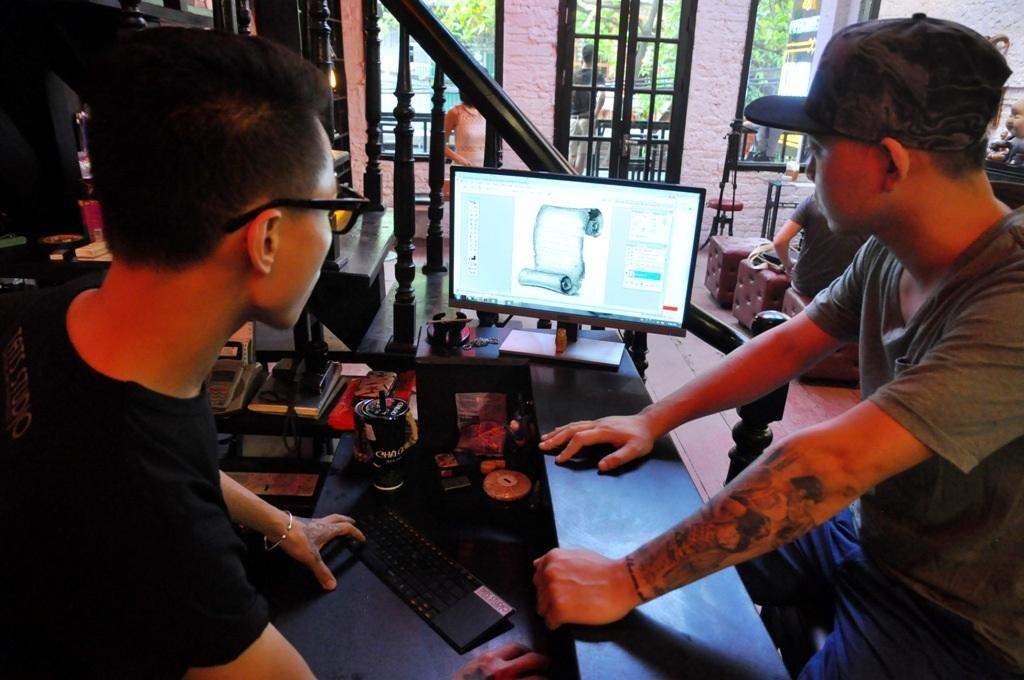 Trong ảnh, anh Đạt cùng anh Tuấn dựng hình đồ họa cho lá thư.