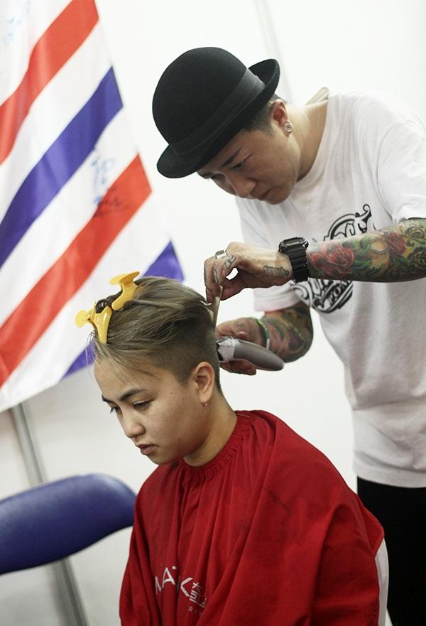Một nghệ sĩ chuẩn bị xăm lên gáy của người mẫu. Công đoạn đầu tiên là cạo hết phần tóc ở vị trí xăm.