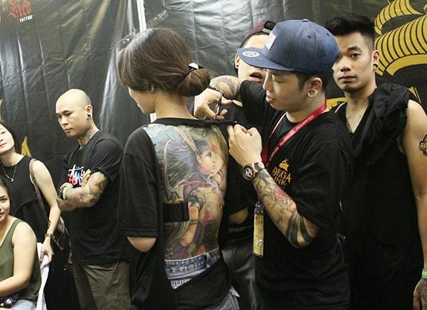 Một người mẫu nữ khác phải hi sinh chiếc áo yêu thích để khoe ra tác phẩm xăm ở lưng