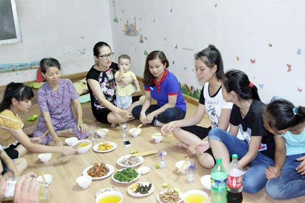 Cô giáo Thúy (bế con) ngồi ăn cơm cùng với các học trò của mình.