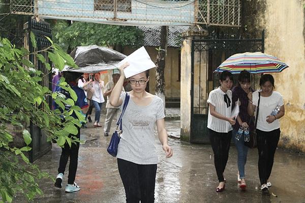 Thí sinh dùng bao đựng giấy tờ để che mưa