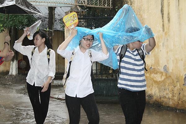 Thí sinh đội mưa tới làm giấy tờ tại điểm thi Đại học Thủy lợi (Hà Nội). (Ảnh: Mai Châm)