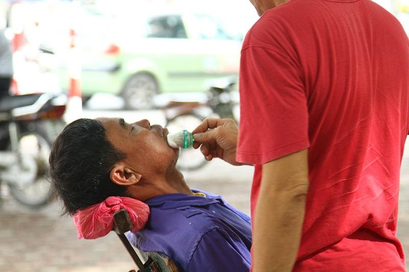 Một phụ huynh đến từ huyện Thanh Oai tranh thủ cắt tóc, cạo râu trong lúc chờ con đi thi.