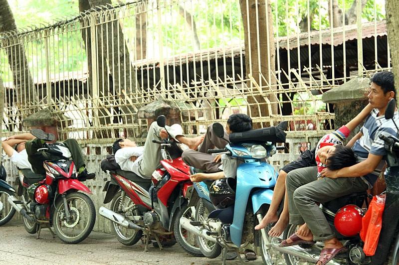 Ở một góc yên tĩnh sát hàng rào, các ông bố nằm nghỉ ngay trên xe máy.