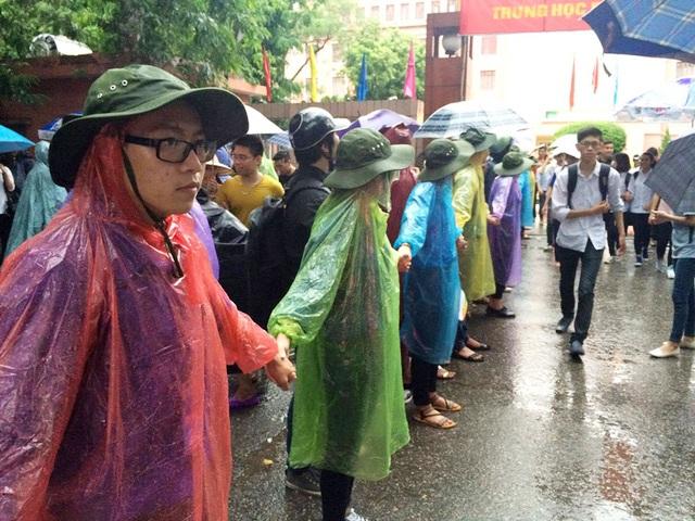 Cảnh SVTN trường Đại học Thủy lợi mặc áo mưa phân luồng giao thông sau giờ thi.