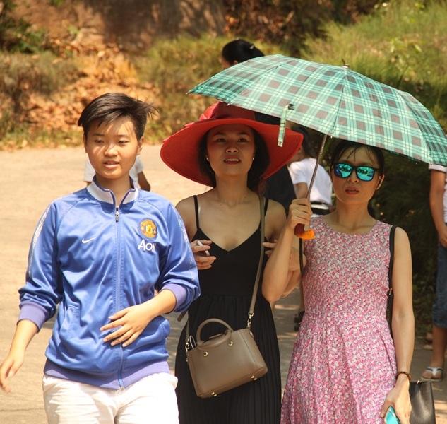 Nhiều cô gái che dù diện váy đẹp du lịch