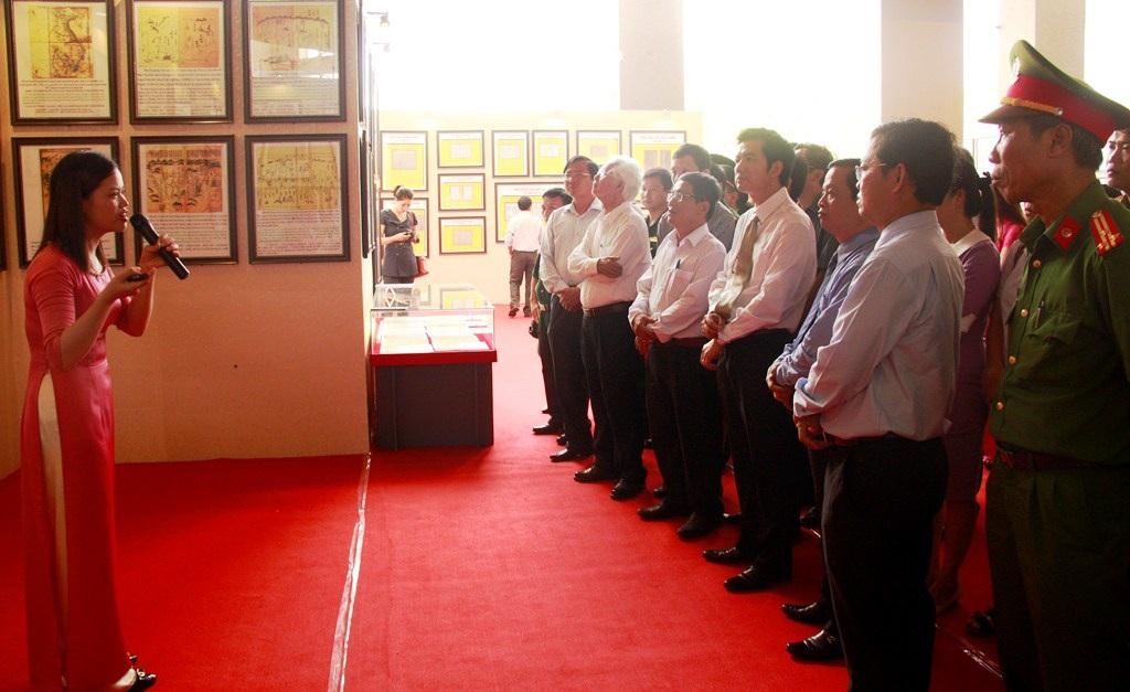 Lãnh đạo các Bộ, tỉnh cùng đông đảo cán bộ, chiến sĩ chăm chú lắng nghe hướng dẫn thuyết trình về những tài liệu trưng bày tại triển lãm