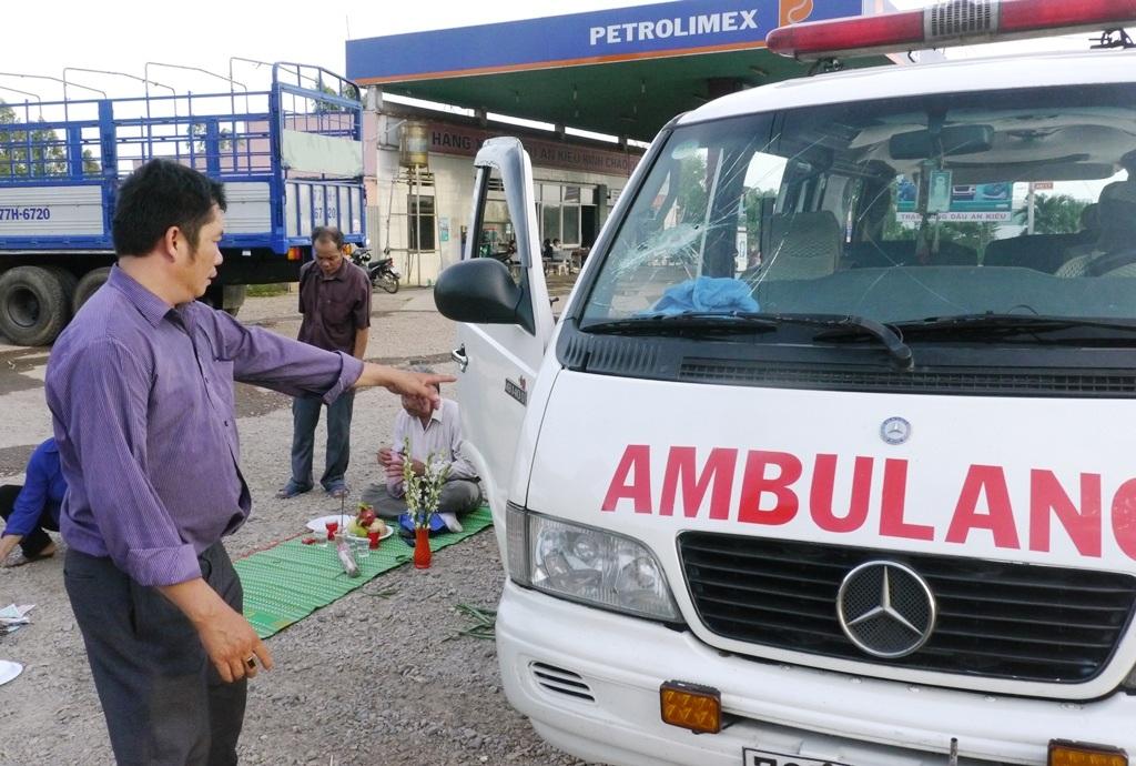 Ông Tuấn chỉ vào vết vỡ kính xe cứu thương do con ông Tạo và một thanh niên khác đập