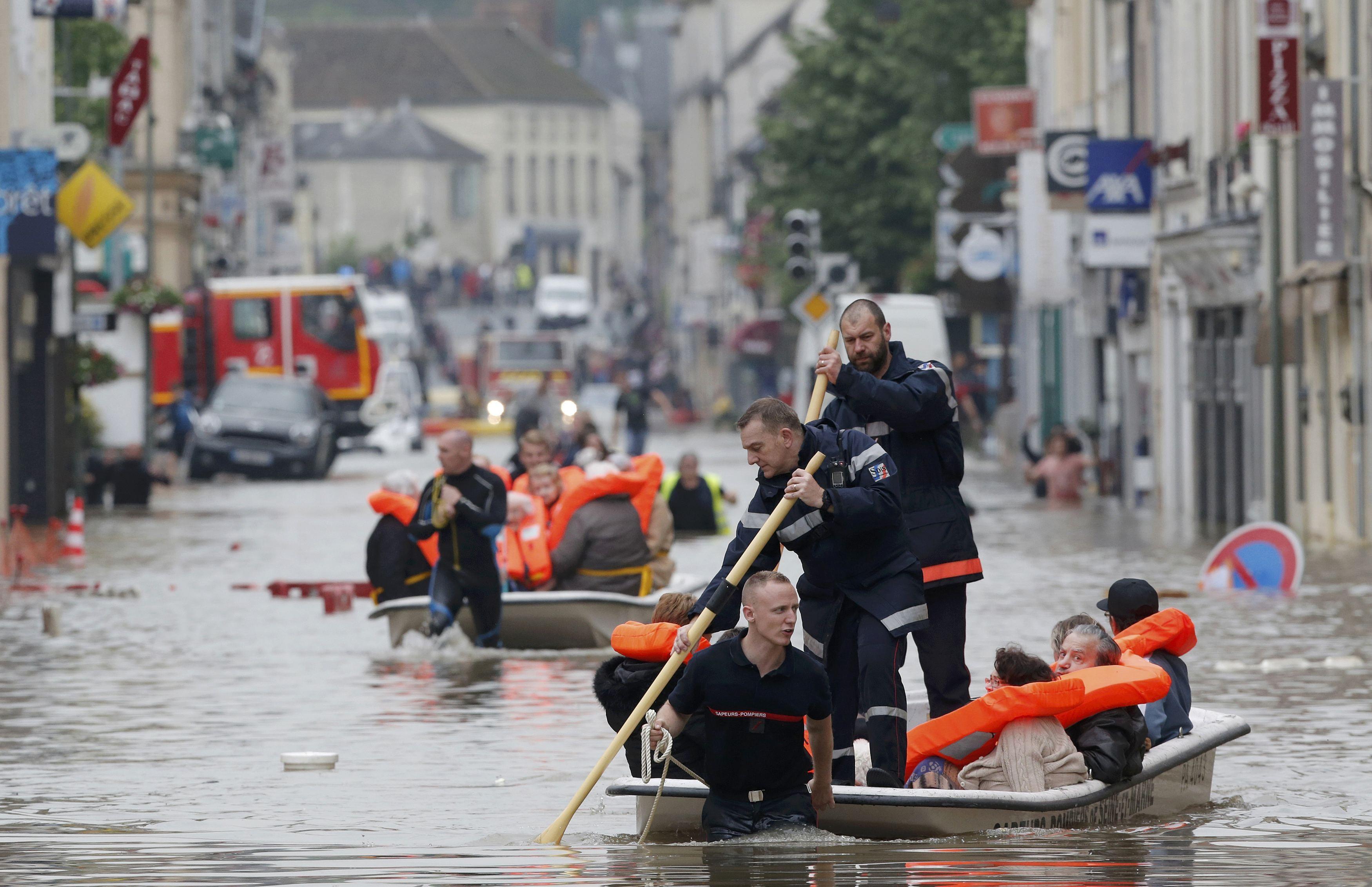 Cảnh sát giúp người dân chèo xuồng sơ tán (Ảnh: Reuters)