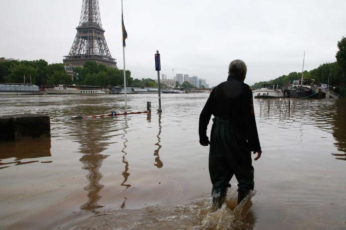 Người dân lội nước gần khu vực tháp Eiffel (Ảnh: Reuters)