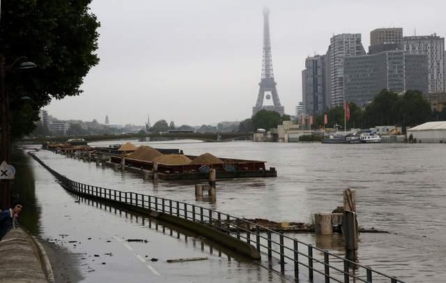 Nước dâng cao tại khu vực gần tháp Eiffel khiến các phương tiện không thể di chuyển (Ảnh: Reuters)