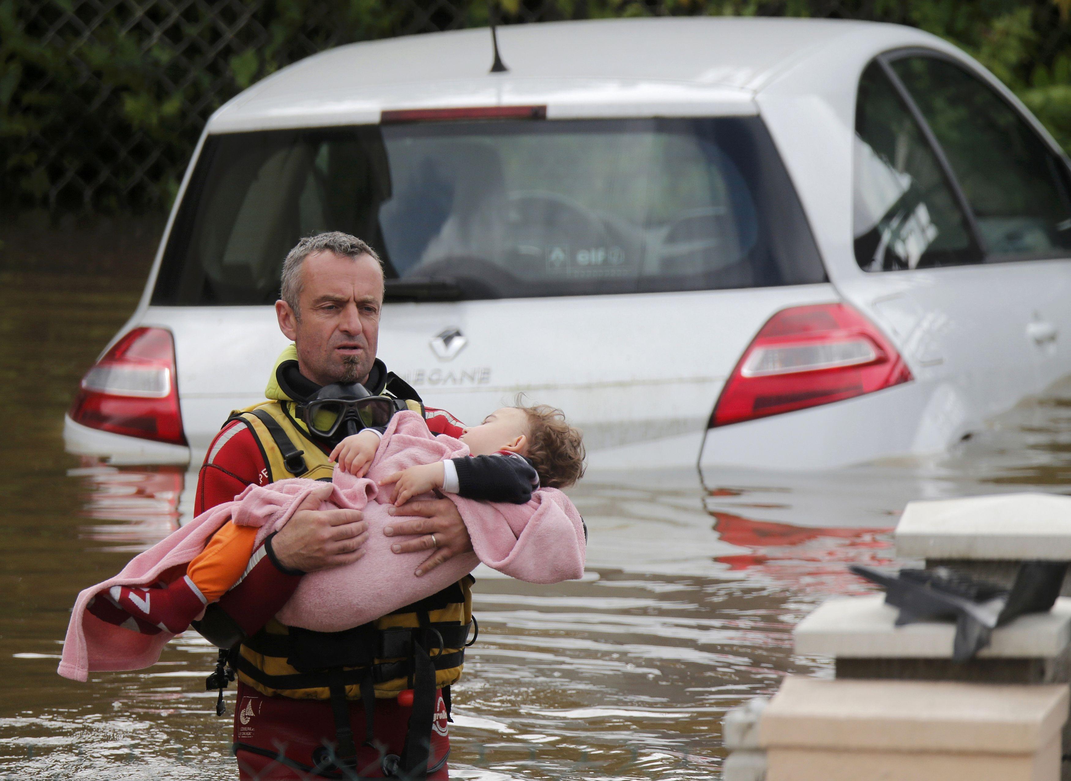 Một em bé được bế ra khỏi ngôi nhà ngập lụt ở Chalette-sur-Loing (Ảnh: Reuters)