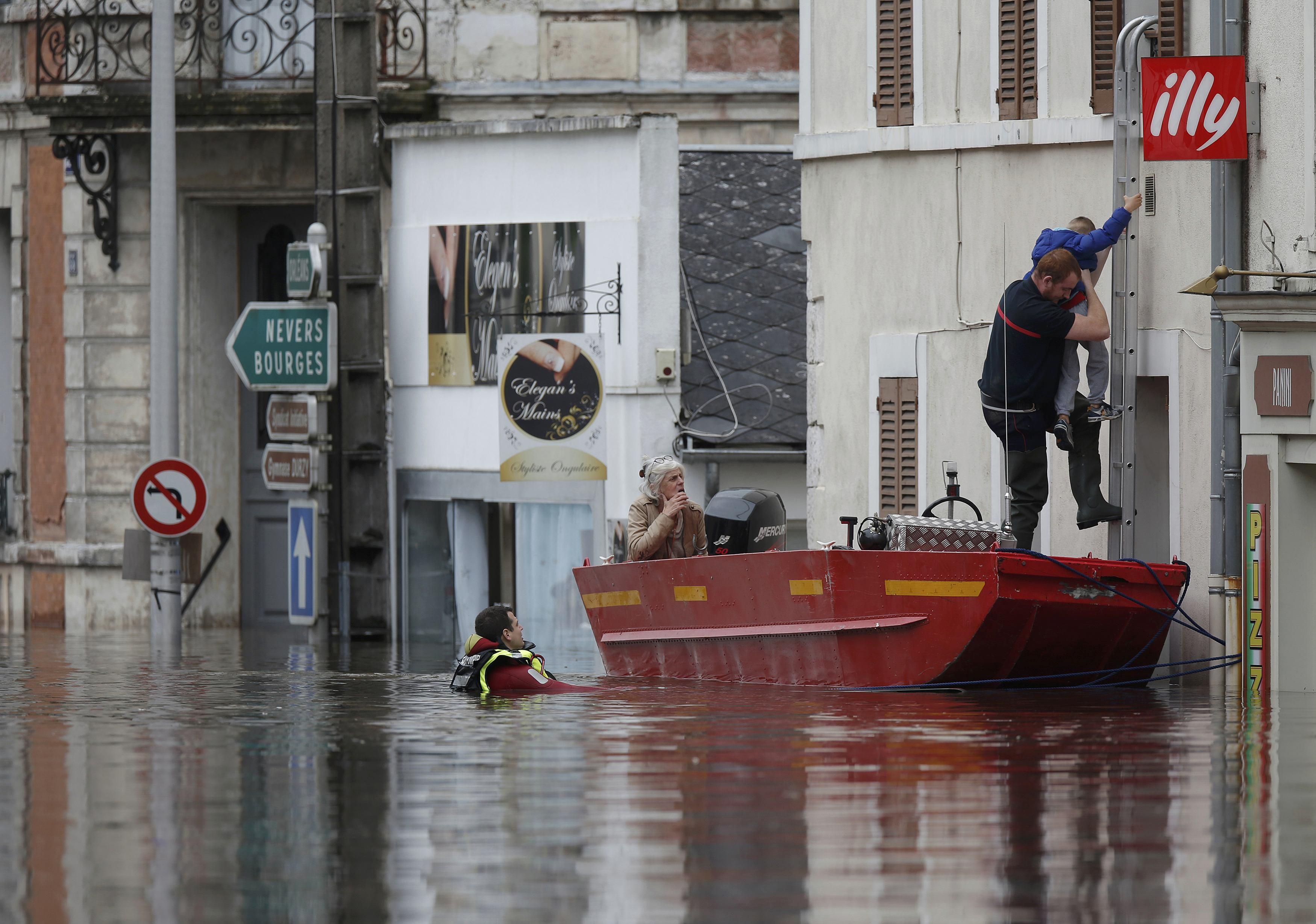 Lính cứu hỏa dùng thuyền đưa người dân sống trên tầng cao của những ngôi nhà ngập lụt ở Montargis tới khu vực an toàn (Ảnh: Reuters)