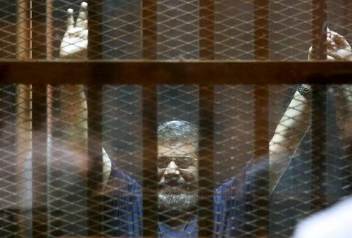 Cựu Tổng thống Mohamed Morsi giơ tay lên trời khi nghe tòa tuyên án hồi năm 2015 (Ảnh: Reuters)