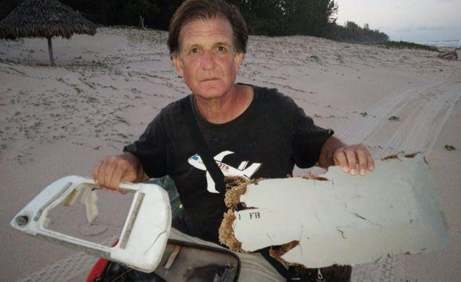 Ông Blaine Gibson chụp cùng các mảnh vỡ nghi của máy bay MH370 tìm thấy ở Madagascar hồi đầu tháng 6. (Ảnh: BBC)