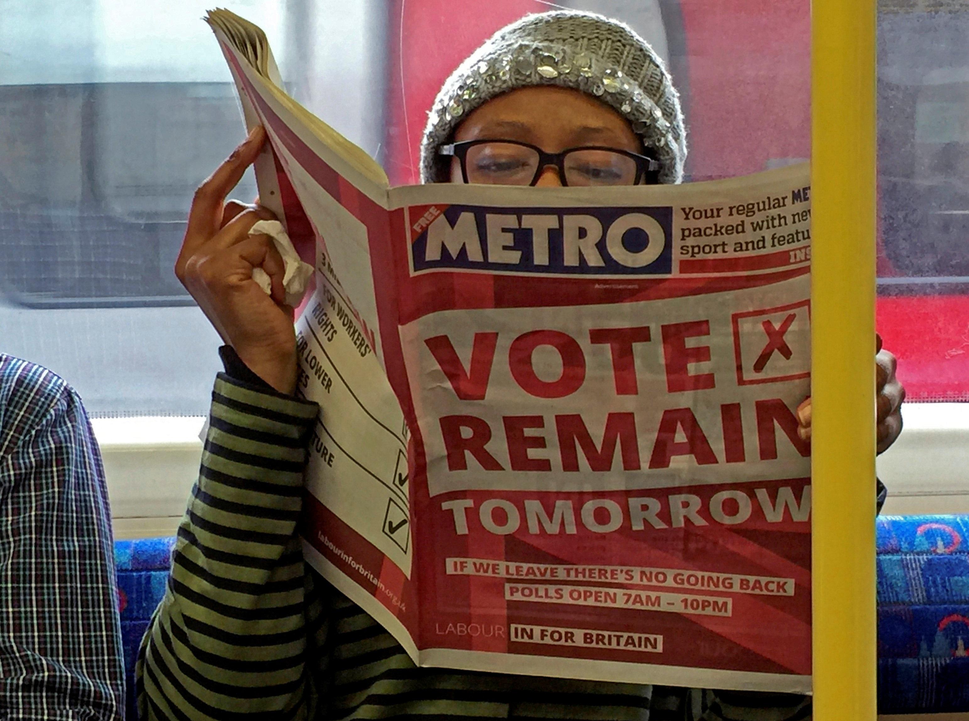 """Một phụ nữ Anh đang đọc báo trên tàu điện ngầm. Dòng quảng cáo """"Bỏ phiếu ở lại"""" xuất hiện ngay trang nhất của tờ báo này (Ảnh: Reuters)"""